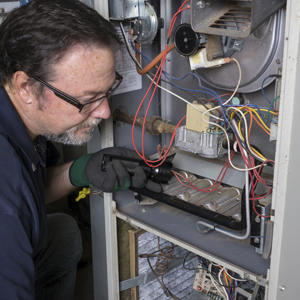 Techician looking over a gas furnace with a flashlight before cleaning it.